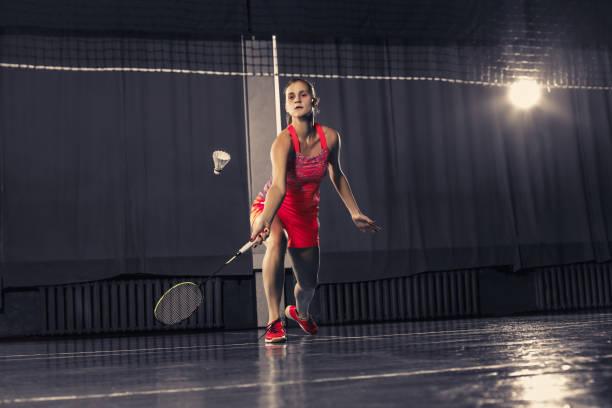 mujer joven jugando a badminton en el gimnasio - bádminton deporte fotografías e imágenes de stock