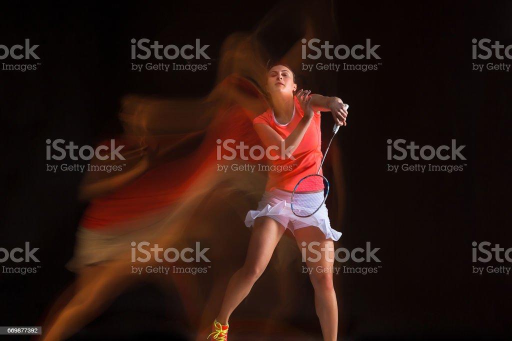 Mujer joven jugando bádminton sobre fondo negro - foto de stock