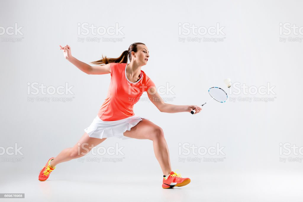 Young woman playing badminton over white background – zdjęcie