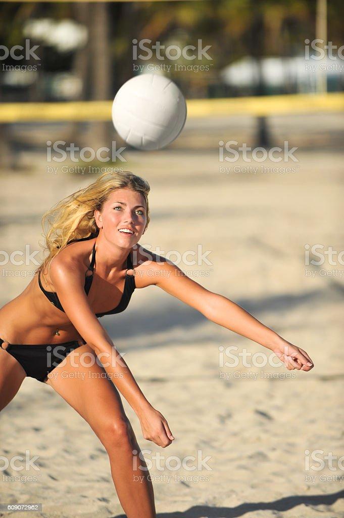 Young woman playing beach volleyball in bikini stock photo