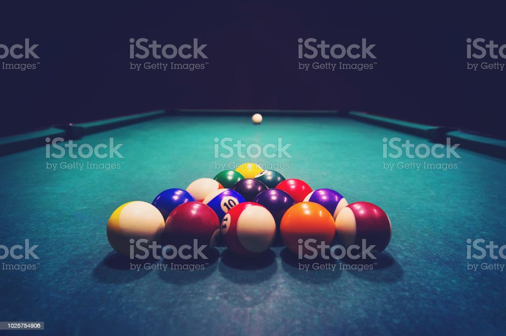 Young woman playing billiards in the dark billiard club. stock photo