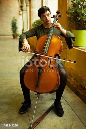 Young woman playing violoncello in a gothic cloister in Barcelona.