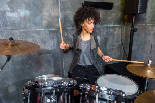 young woman playing drums in musical studio, drummer rock concept stock photo