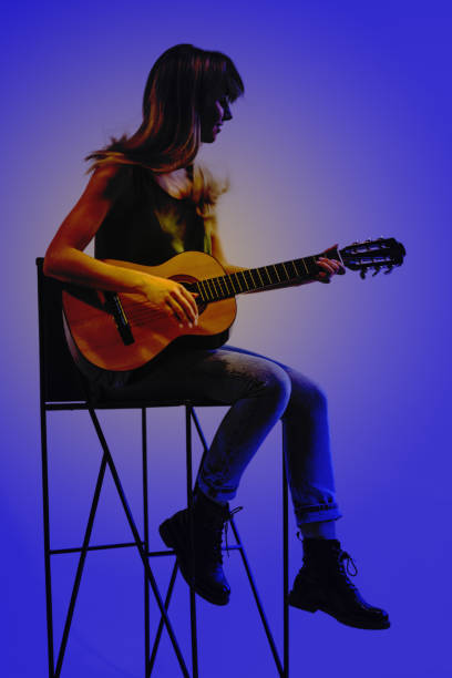 Young woman playing guitar. Blue background stock photo