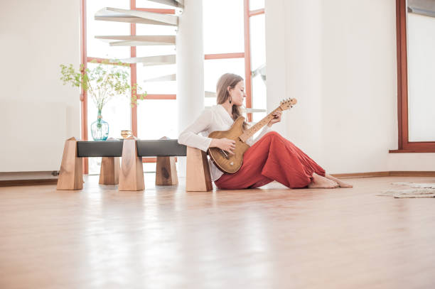 Young Woman Playing Guitar in the New Home – zdjęcie