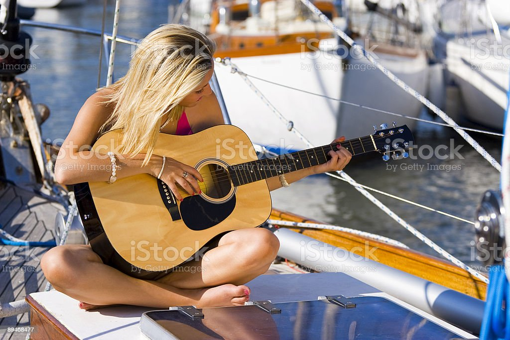 Young Woman Playing Guitar on A Boat royalty free stockfoto