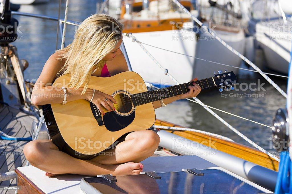 Jeune femme jouer de la guitare sur un bateau photo libre de droits