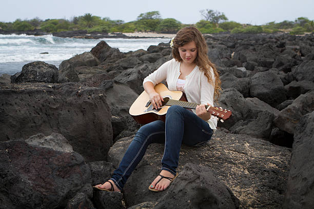 Young Woman Playing Guitar Teen girl sitting on lava rocks playing the guitar at the seashore in Hawaii. neicebird stock pictures, royalty-free photos & images