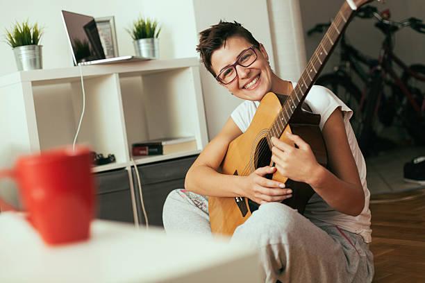 junge frau spielt gitarre - marko skrbic stock-fotos und bilder