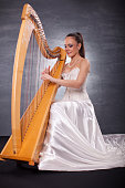 Young woman playing harp. She is wearing a very long white satin skirt and white corset and she looks very happy