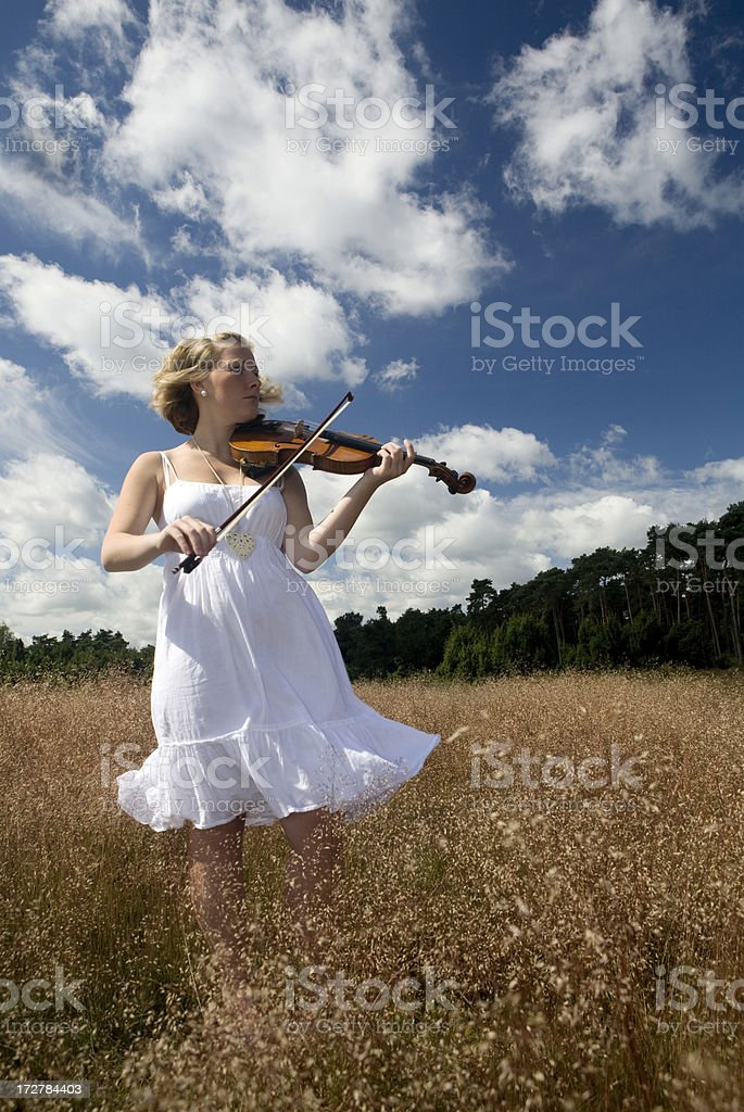 Young woman playing her violin outdoor royalty-free stock photo
