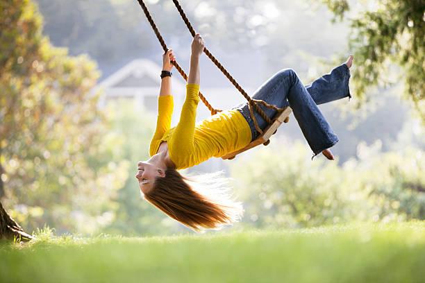jovem mulher jogando em um balanço - balouço imagens e fotografias de stock
