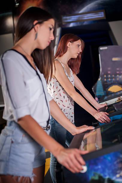 young woman playing on the pinball machine - pinball spielen stock-fotos und bilder