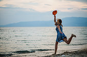 istock Young woman playing paddle ball at the beach 1266078604