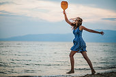 istock Young woman playing paddle ball at the beach 1266078656