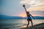 istock Young woman playing paddle ball at the beach 1266078904