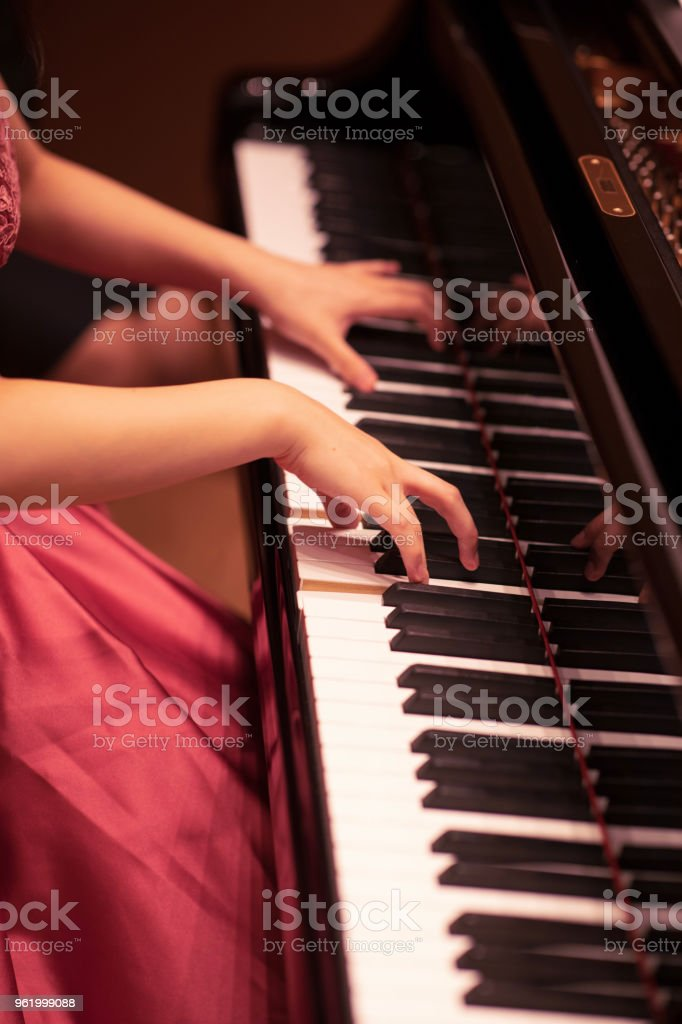 Young woman playing piano in concert