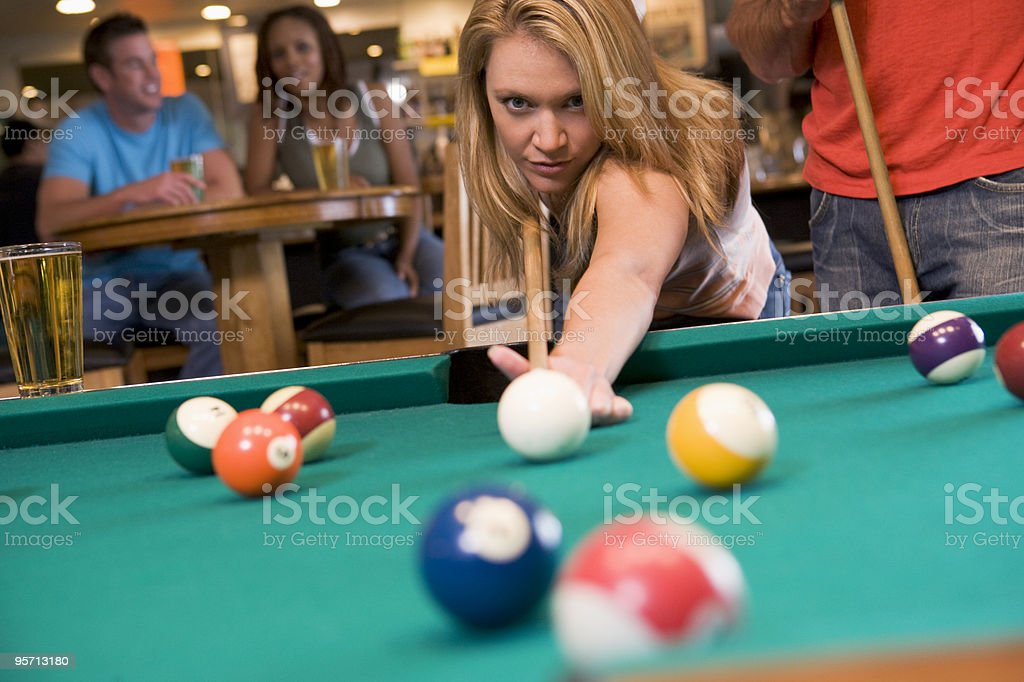 A young woman playing pool in a club royalty-free stock photo
