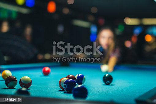 istock Young woman playing pool 1134534154