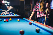 Young brunette woman is leaning on a pool table during a game