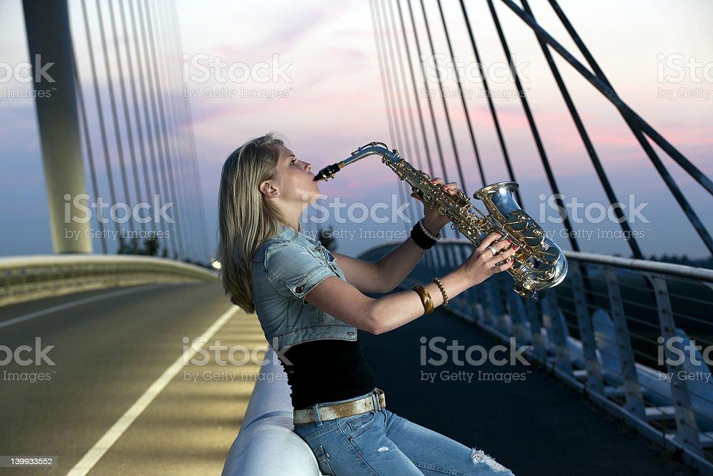 young woman playing saxophone on illuminated bridge XXXL stock photo