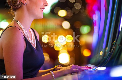 istock Young woman playing slot machines at the Casino 468241368