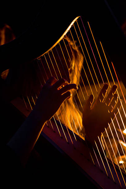 young woman playing the harp - harpist stock photos and pictures