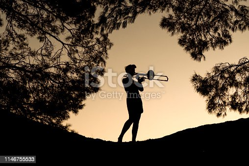 Young woman playing trombone at sunset