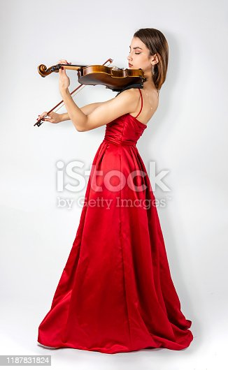Young woman playing violin standing with eyes closed