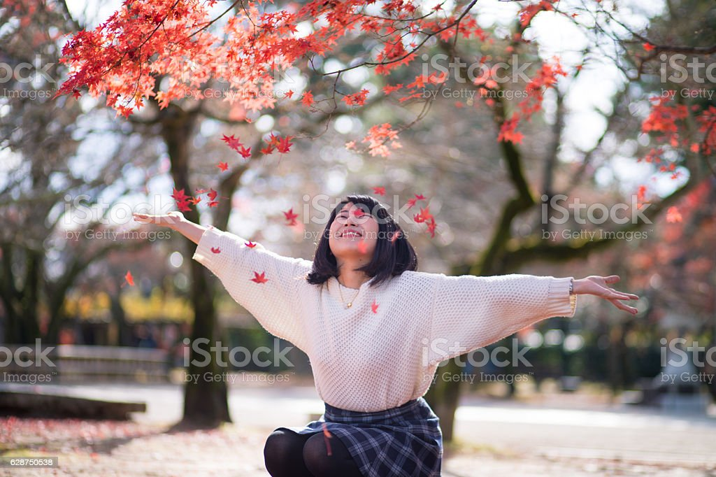 Young woman playing with autumn leaves stock photo