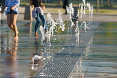 Photography of barefoot girls touching the fountain by legs.  Image with defocued background. Concepts of walking, happiness, childhood and freshness in hot summer day.