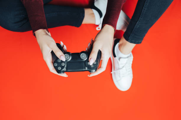 young woman playing with gamepad on red. - telecomando background foto e immagini stock