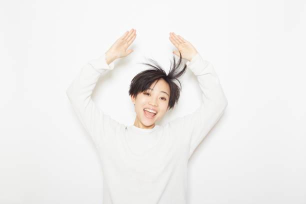 彼女は髪を演奏若い女性 - スタジオ 日本人 ストックフォトと画像