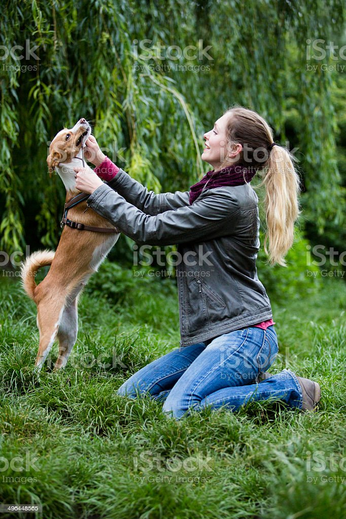 Young woman playing with her little dog royalty-free stock photo
