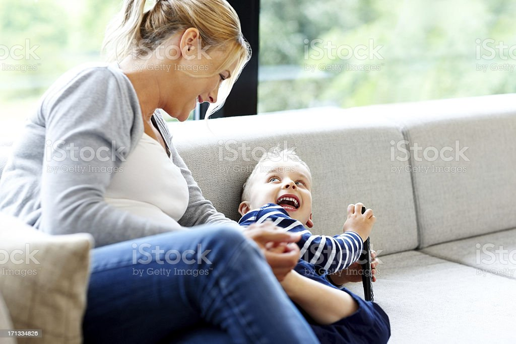 Young woman playing with her son at home royalty-free stock photo