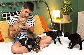 istock Young woman playing with puppies and cat 1066865628