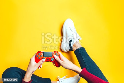 Young thin woman playing with red gamepad, sitting on yellow background. flat lay.