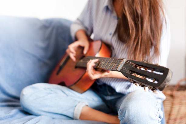Young woman plays guitar. Happy girl enjoying music. Female musician smiling at home. stock photo
