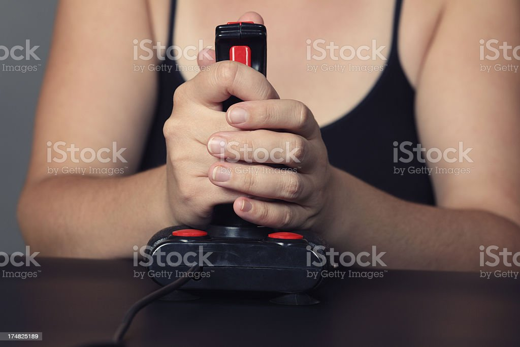 Young woman plays video game with a retro joystick royalty-free stock photo