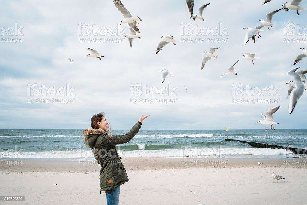 Joven mujer juega con gaviotas en el Báltico - foto de stock