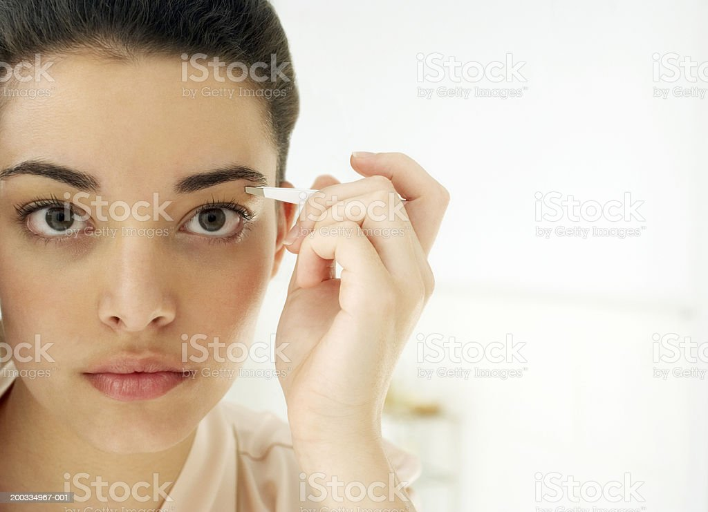 Young Woman Plucking Eyebrows Closeup Reflection In Mirror Stock