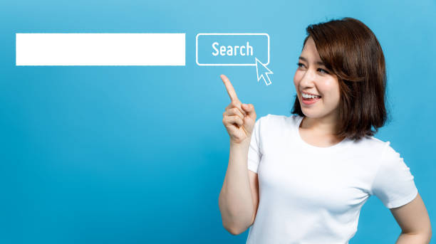 young woman pointing at the search bar. young woman pointing at the search bar. reference book stock pictures, royalty-free photos & images