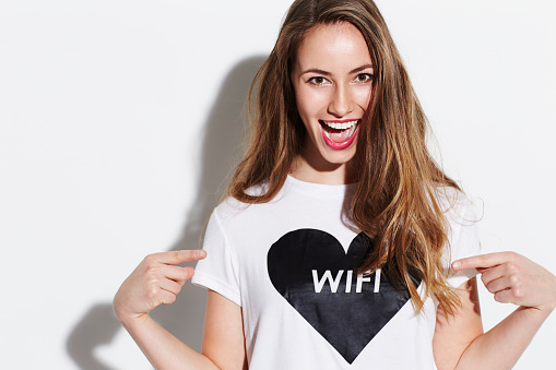 Young woman pointing at t-shirt, smiling