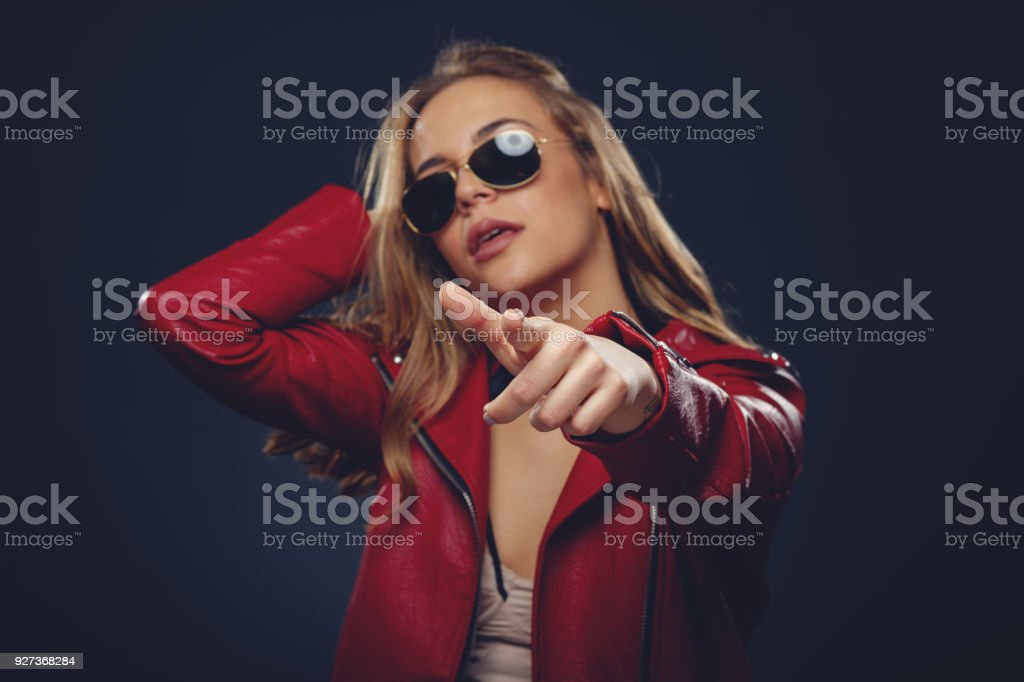 Young woman pointing at you in studio on dark stock photo