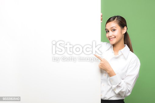 933380808 istock photo Young woman pointing message board. 933380540