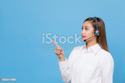 933380808istockphoto Young woman pointing something. 933347696