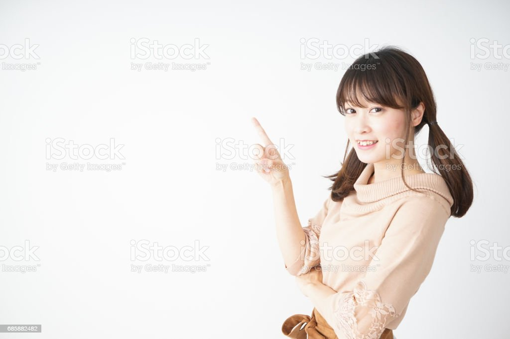 Young woman pointing something with smile stock photo