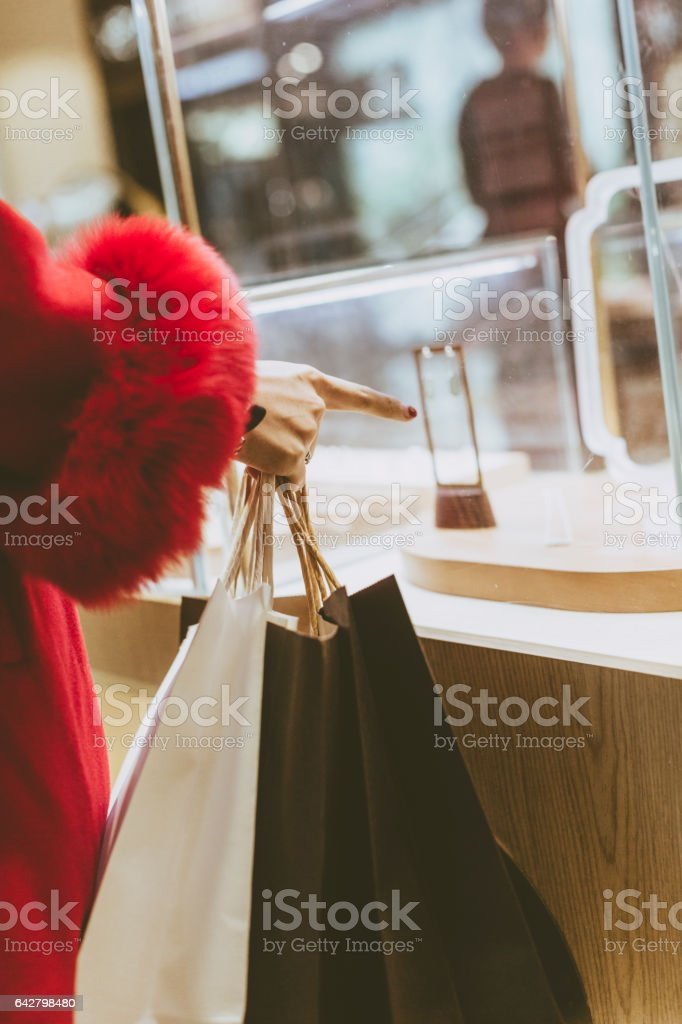 young woman pointing to the jewelry window display stock photo