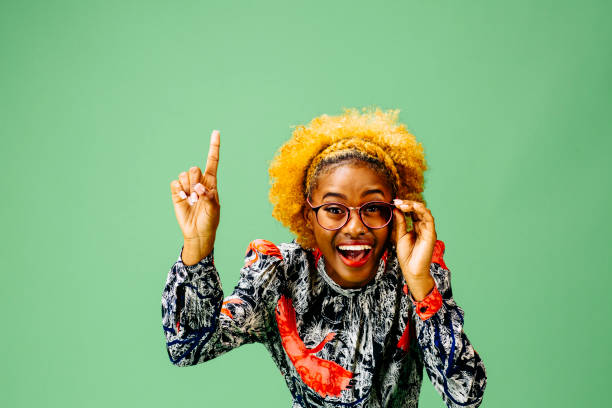 Young woman pointing up and holding her glasses, Young woman pointing up and holding her glasses, isolated on green studio background nerd hairstyles for girls stock pictures, royalty-free photos & images