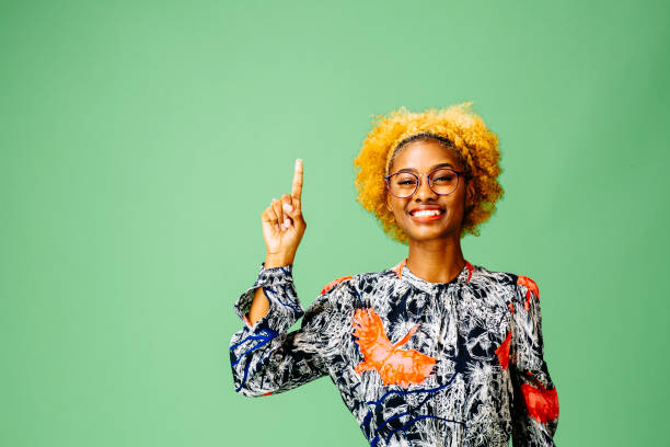 Young woman pointing up Young woman pointing up amd smiling at camera, isolated on green studio background nerd hairstyles for girls stock pictures, royalty-free photos & images